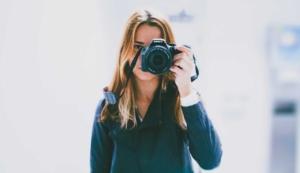 Photographer standing behind camera